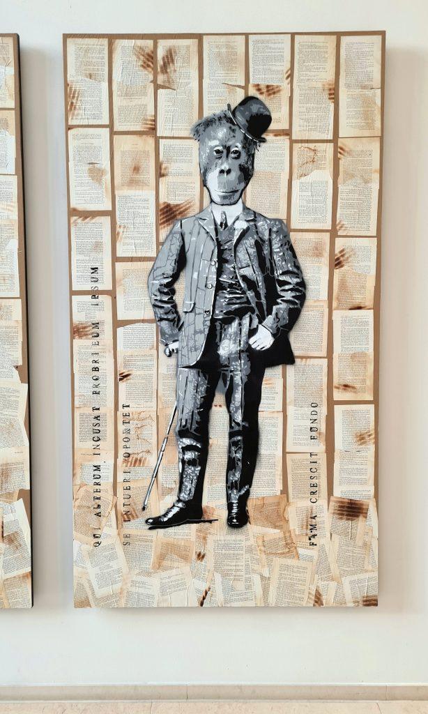 Übersicht der Stencil Arbeiten in Hamburg an der Alster, das Bild zeigt Chimäre, das heißt Fabelwesen mit Tierköpfen und Menschenkörper, Diese Form des Graffiti ist aus Schablonen und Sprühdose entstanden. Es hält sich in Scwarz-weiß und mehreren Grautönen. Hier ist der Kopf eines Affens mit Hut zu sehen mit dem Körper eines Mannes in klassischer Kleidung des 19. Jahrhunderts.
