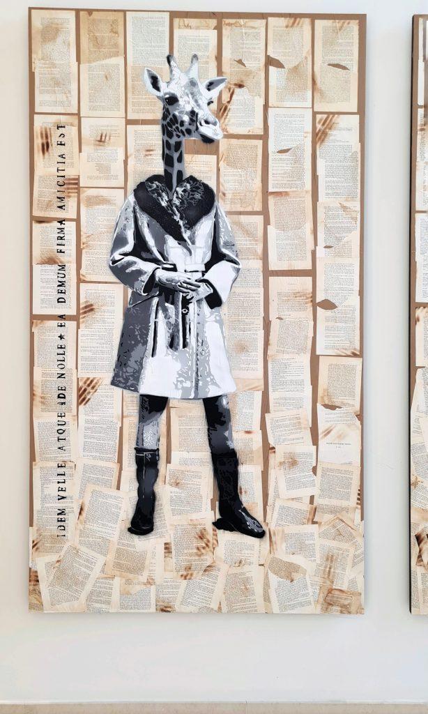 Übersicht der Stencil Arbeiten in Hamburg an der Alster, das Bild zeigt Chimäre, das heißt Fabelwesen mit Tierköpfen und Menschenkörper, Diese Form des Graffiti ist aus Schablonen und Sprühdose entstanden. Es hält sich in Scwarz-weiß und mehreren Grautönen. Hier ist der Kopf einer Giraffe zu sehen mit dem Körper einer Frau in klassischer Kleidung der Mitte des 20. Jahrhunderts Jahrhunderts.