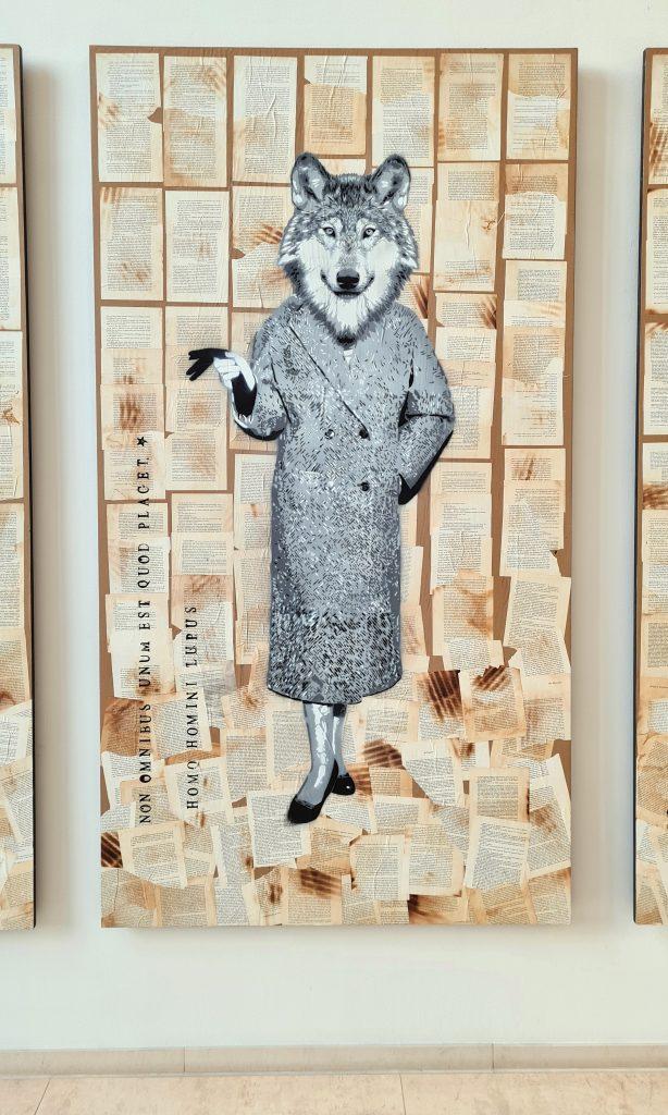 Übersicht der Stencil Arbeiten in Hamburg an der Alster, das Bild zeigt Chimäre, das heißt Fabelwesen mit Tierköpfen und Menschenkörper, Diese Form des Graffiti ist aus Schablonen und Sprühdose entstanden. Es hält sich in Scwarz-weiß und mehreren Grautönen. Hier ist der Kopf eines Wolfes zu sehen mit dem Körper einer Frau in klassischer Kleidung der Mitte des 20. Jahrhunderts Jahrhunderts.